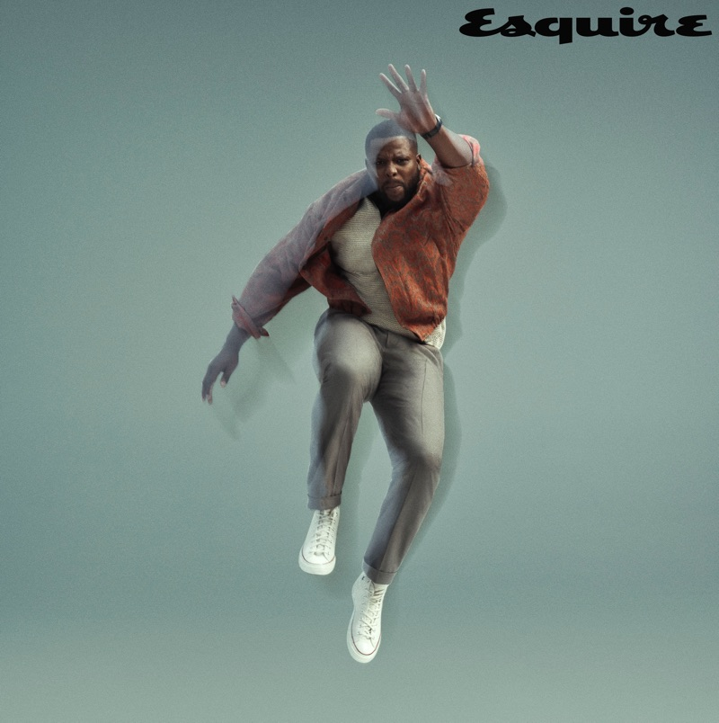 Jumping, Winston Duke rocks a Dries Van Noten jacket, Rag & Bone polo, Converse sneakers, and Gucci pants.