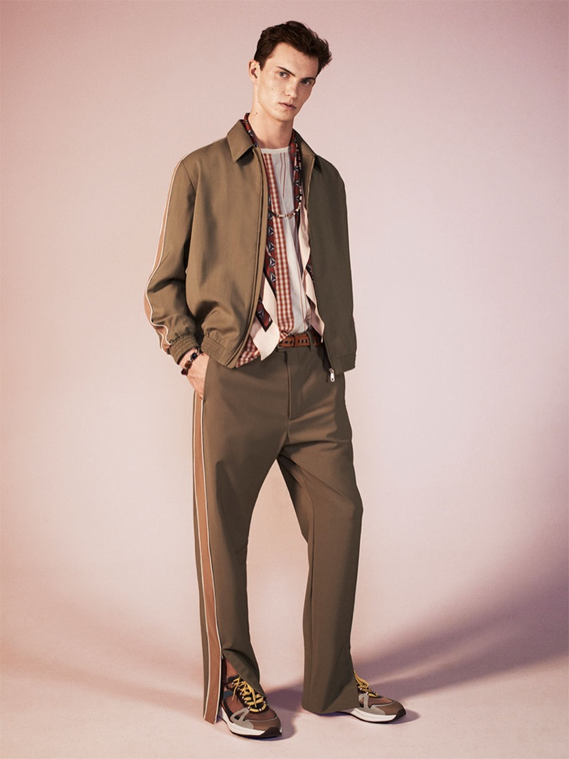 Luc Defont-Saviard dons a tan tracksuit with a paneled t-shirt, silk scarf, and sneakers from Zara's spring-summer 2019 studio collection.