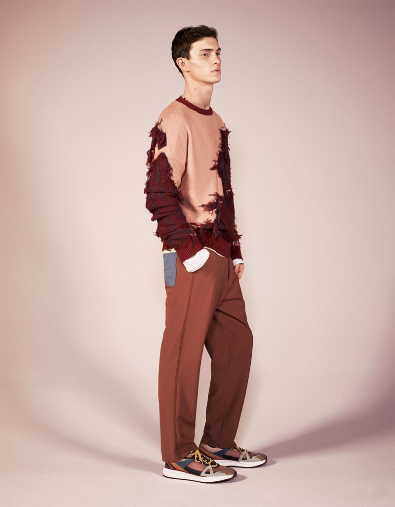 Making a fashion statement, Luc Defont-Saviard models Zara's deconstructed sweater, trousers, and sneakers from its spring-summer 2019 studio collection.