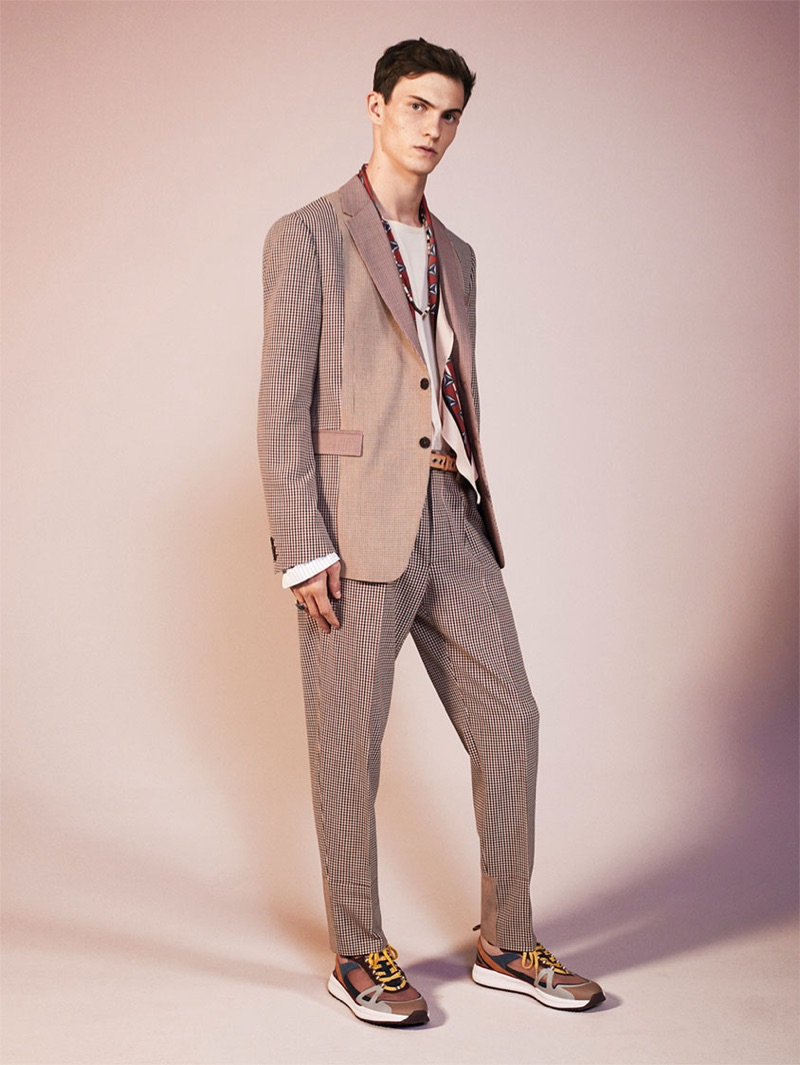 Donning a mixed pattern suit and sneakers, Luc Defont-Saviard rocks a look from Zara's spring-summer 2019 studio collection. His outfit also includes the brand's classic t-shirt and a silk scarf.