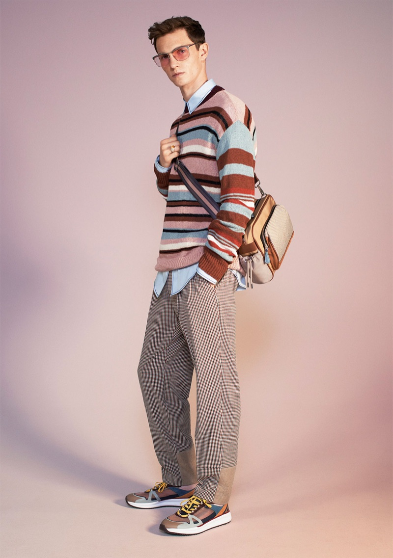 Standing out, Luc Defont-Saviard wears a striped sweater, mixed sartorial trousers, shirt, sneakers, sunglasses, and a bag from Zara's spring-summer 2019 studio collection.