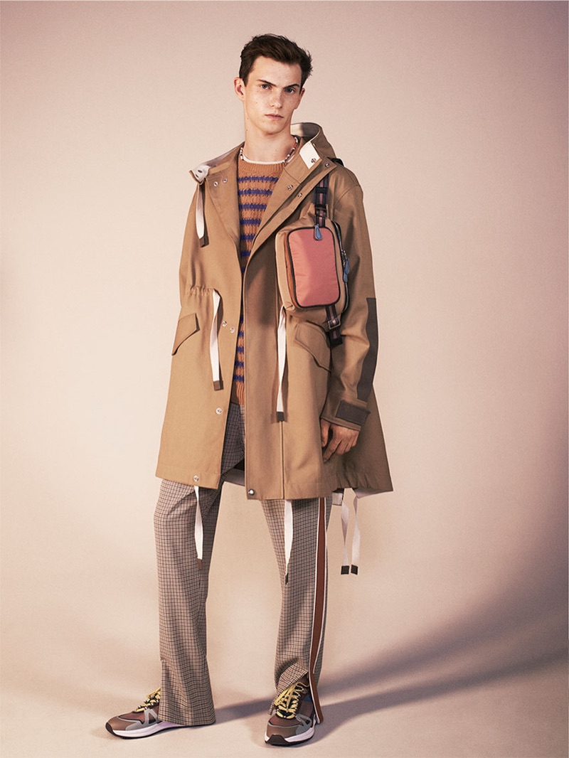 Embracing a fashionable cool, Luc Defont-Saviard sports a parka, striped sweater, sartorial track pants, belt bag, and sneakers from Zara's spring-summer 2019 studio collection.