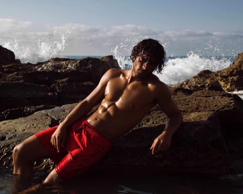 Sporting red swim shorts, Matteo Cupelli fronts Azzaro Paris' spring-summer 2019 swimwear campaign.