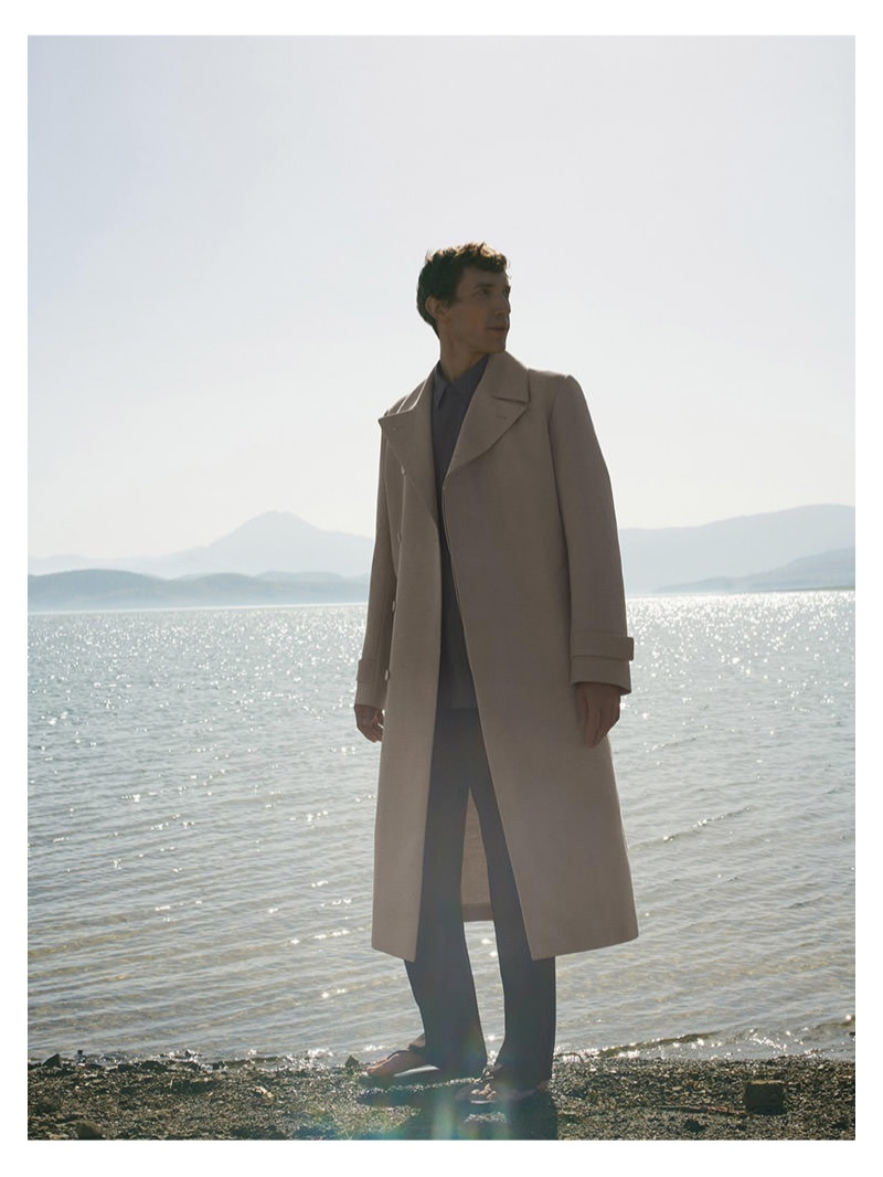 Donning a sleek coat, Thilo Muller fronts COS' spring-summer 2019 campaign.