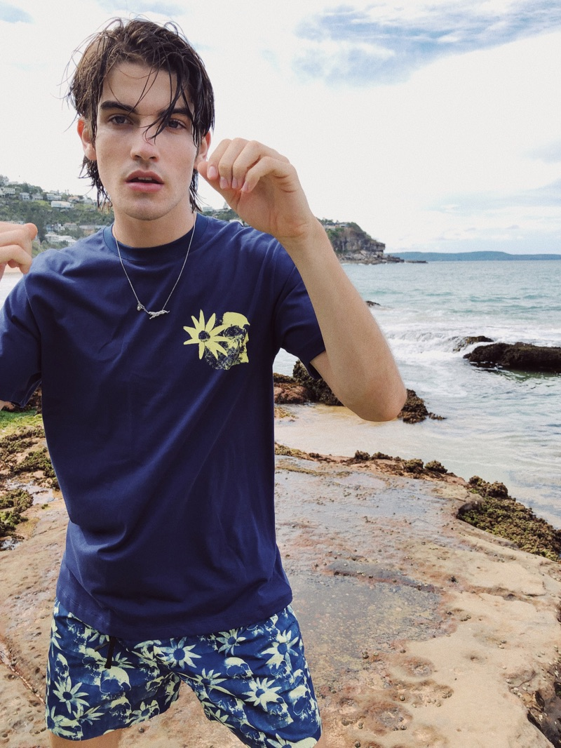Sporting pieces from East Dane's exclusive Double Rainbouu capsule, Cal Fernie wears a short-sleeve tee and swim shorts.