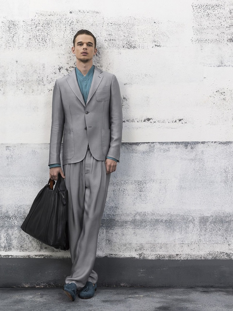 Embracing relaxed tailoring, André Bona dons a grey suit from Giorgio Armani.