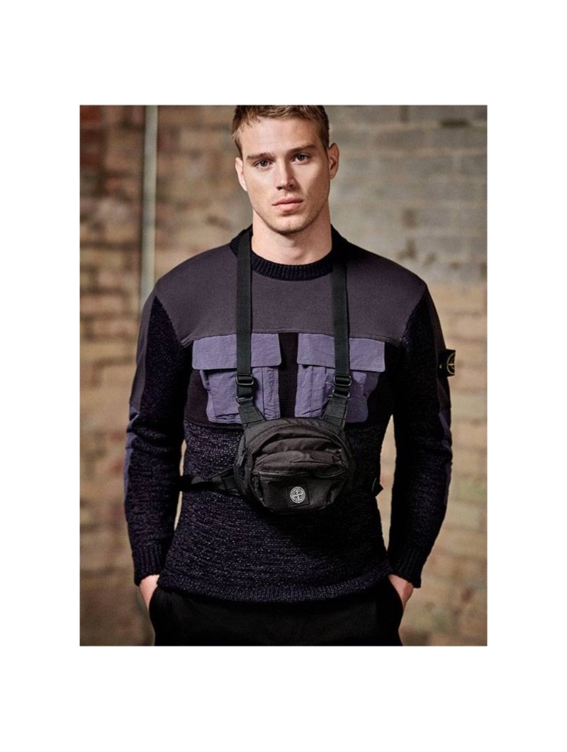 Matthew Noszka wears a Stone Island mixed-media sweater with a utility belt bag and Acne Studios shorts.
