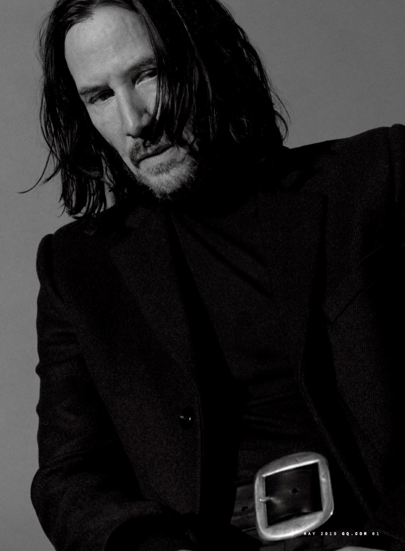 Actor Keanu Reeves wears a Saint Laurent coat, Bottega Veneta turtleneck, and Artemas Quibble belt.