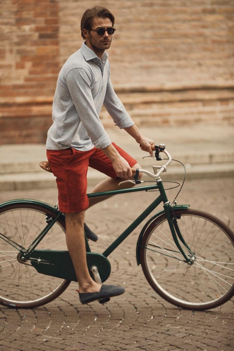 Riding a bike, Jacey Elthalion models Luca Faloni's Brera polo shirt.