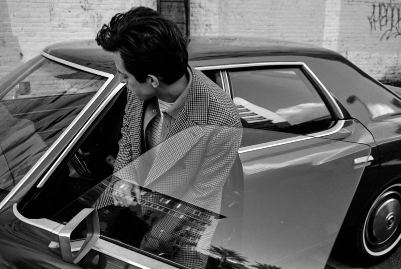Getting into a vintage car, Mark Ronson wears a Brunello Cucinelli double-breasted houndstooth jacket and Neighborhood suede overshirt. He also dons a Handvaerk striped t-shirt and Prada trousers.