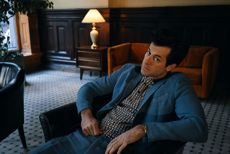 Sitting for a photo, Mark Ronson wears a blue Boglioli suit with a Valentino logo polo shirt.