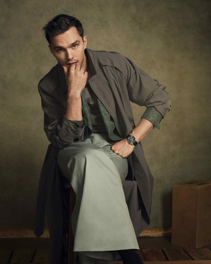 Nicholas Hoult dons a BOSS coat and leather vest with a Daks linen jacket and trousers.  He also sports a Jaeger-LeCoultre watch.