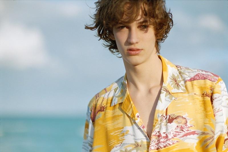 Taking to the beach, Niks Gerbasevskis wears a yellow Hawaiian shirt by Pull & Bear.