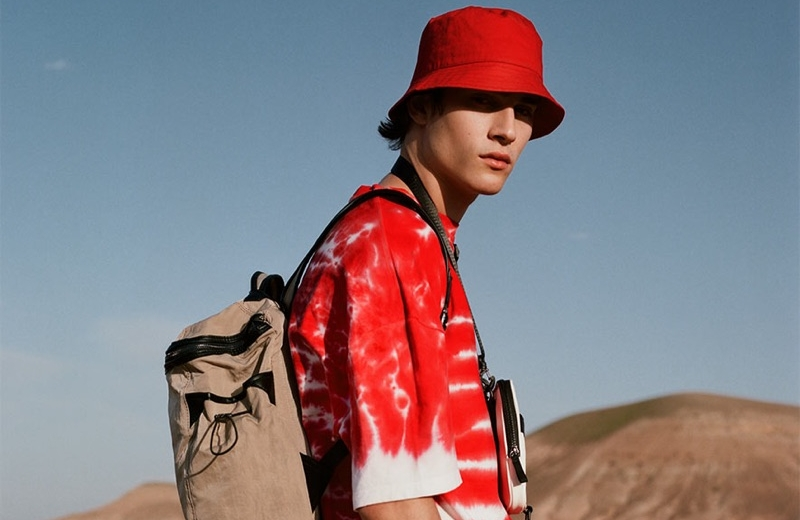 Rocking red, Liam Kelly sports a tie-dye print t-shirt with a bucket hat and white pants by Reserved.