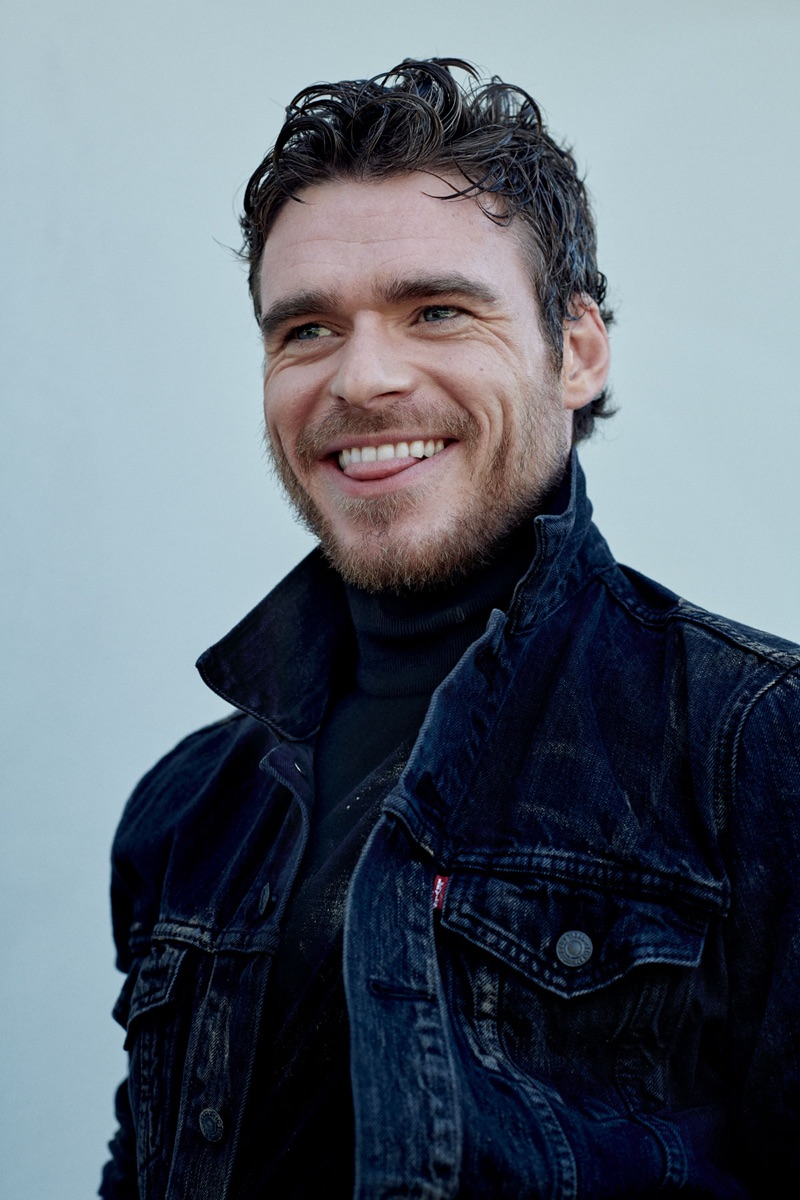 All smiles, Richard Madden wears a denim jacket by Levi's with a Prada turtleneck.