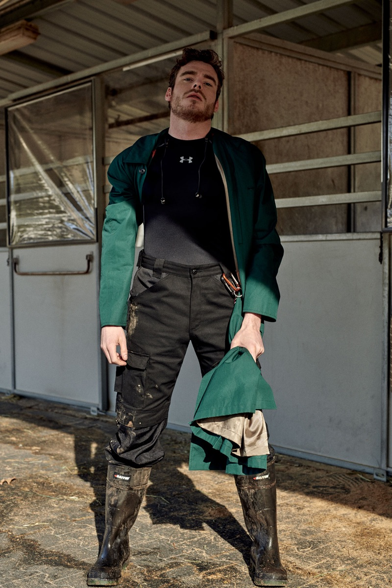 Getting his hands dirty, Richard Madden wears a Gucci coat with a top by Under Armour. He also sports Cat pants and Baffin boots.