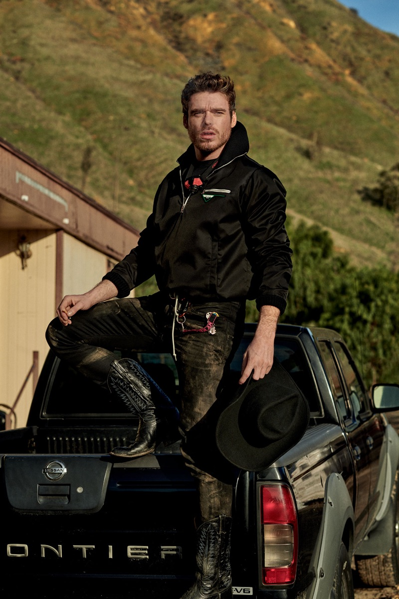 Actor Richard Madden wears a Prada jacket, Under Armour top, Saint Laurent jeans, and a Red Wing belt. He also rocks cowboy boots from The Universal Studios Costume Department.