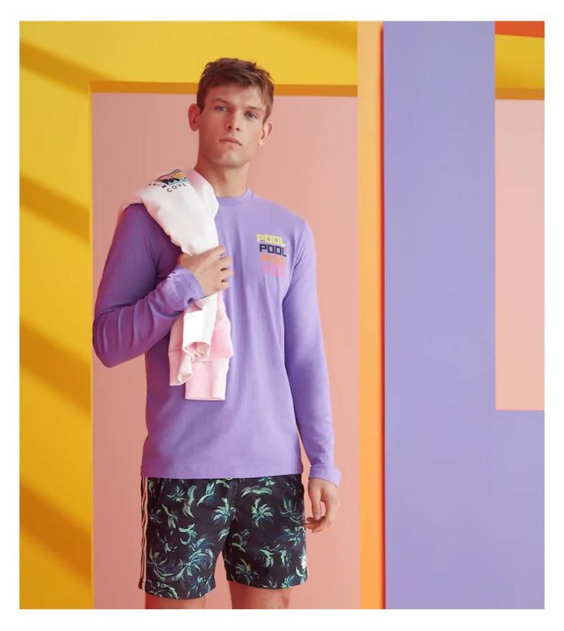 Elliott Reeder sports a purple print t-shirt and palm print swim shorts by Scotch & Soda.