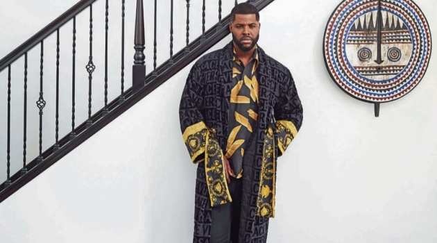 Winston Duke wears a Versace bathrobe, Dolce & Gabbana shirt, Saturdays New York sweatpants, and Falke socks.
