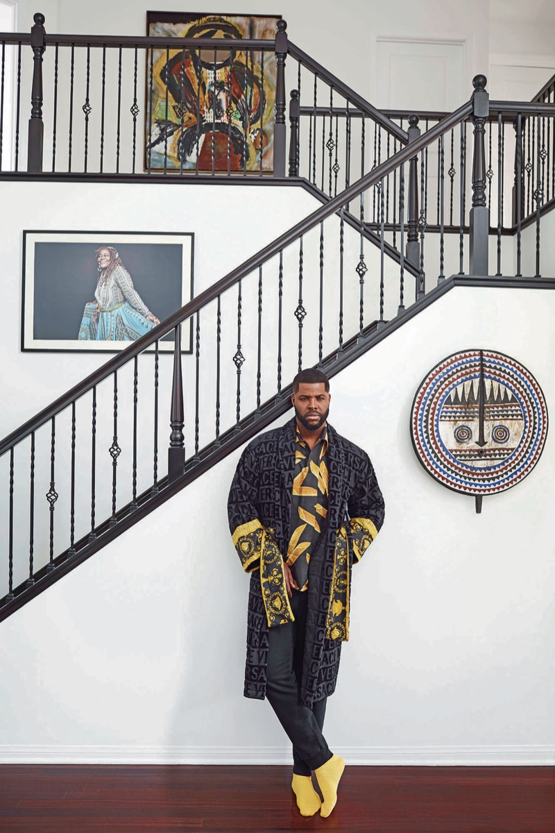 Winston Duke wears a Versace bathrobe, Dolce & Gabbana shirt, Saturdays New York sweatpants, and Falke socks.