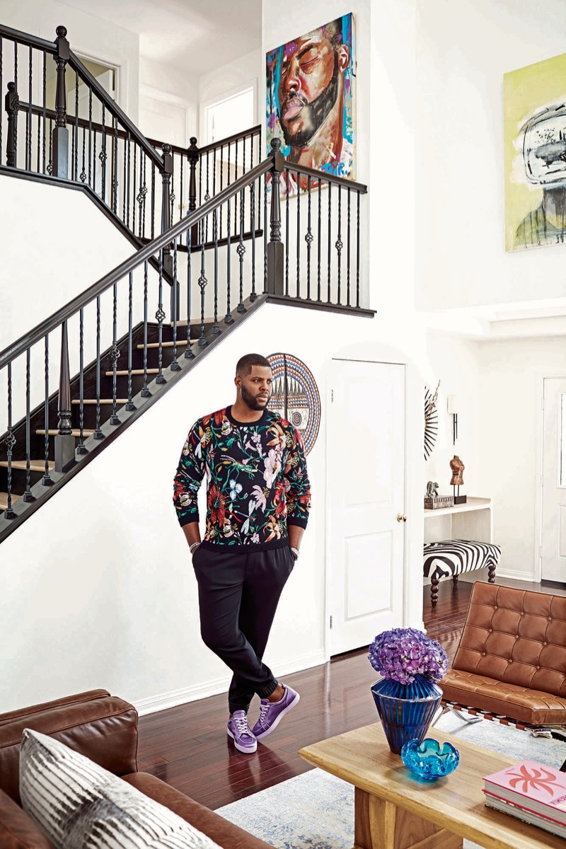 Posing in his home, Winston Duke wears a Gucci sweater, Dolce & Gabbana joggers, and Christian Louboutin sneakers. A David Yurman bracelet and TAG Heuer watch completes his look.