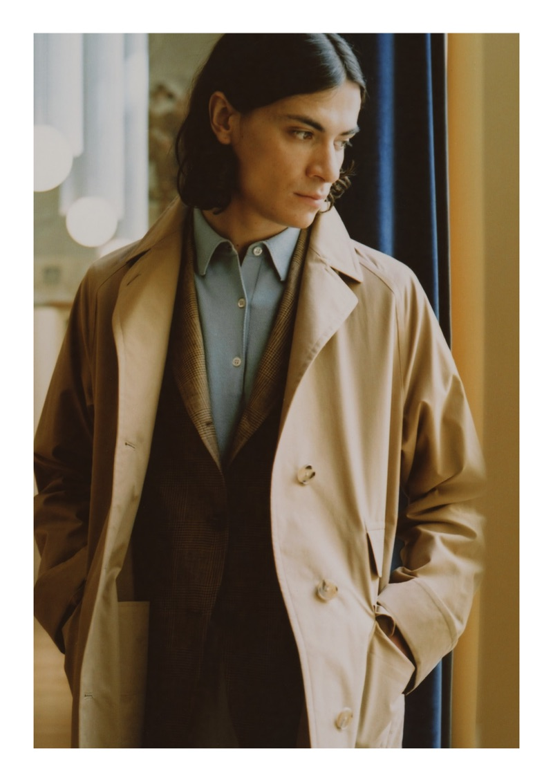 Coco Roussel wears a Cohérence overcoat, Drake's jacket, John Smedley polo, Ring Jacket trousers, and Doek sneakers.
