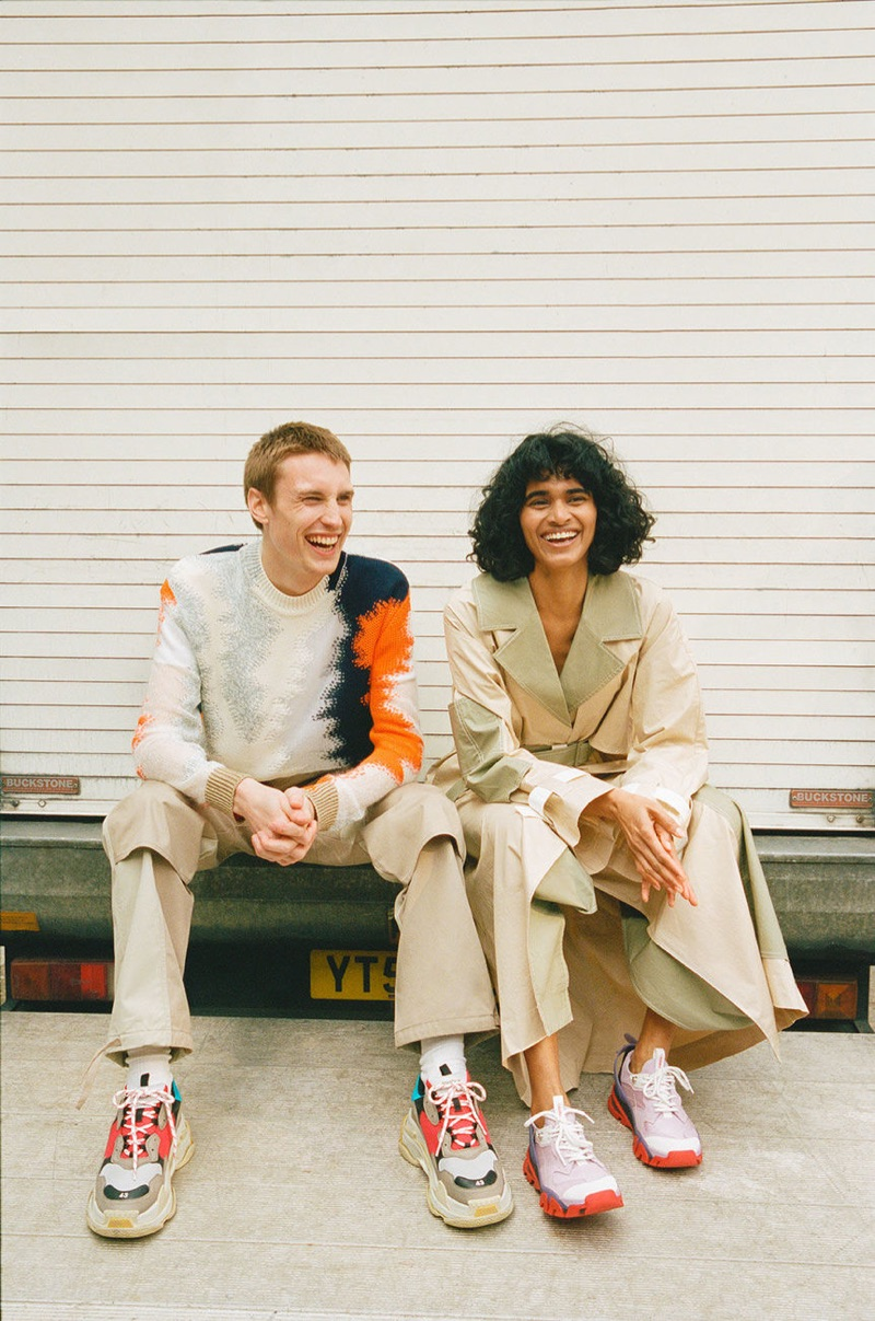 Sitting for a photo, Michael Sharp rocks a Jil Sander sweater, Jacquemus trousers, and Balenciaga sneakers.