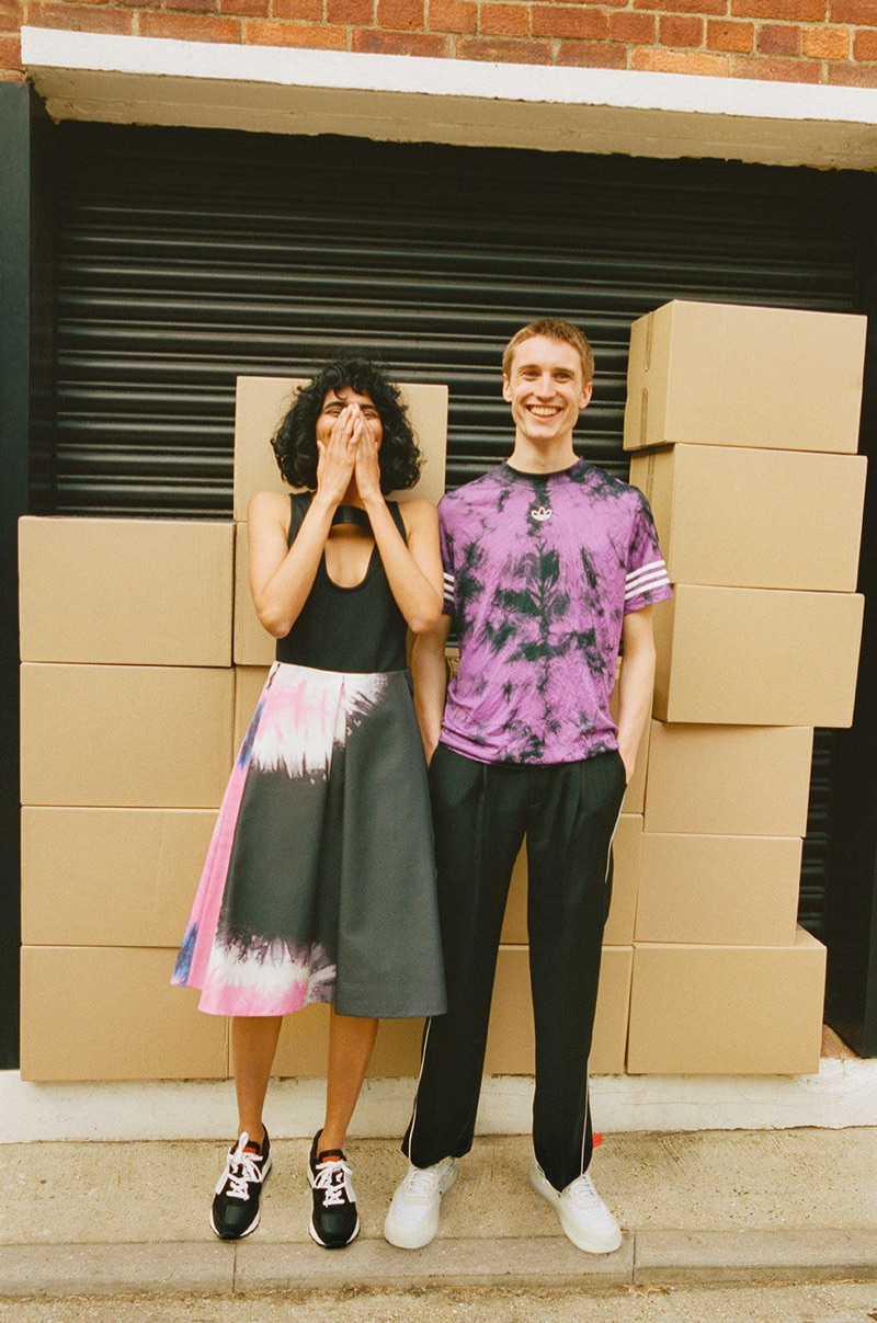Posing for a picture with Radhika Nair, Michael Sharp wears an Adidas t-shirt, Ader Error trousers, and sneakers from Stadium Goods.