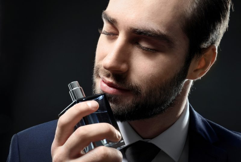 Dapper Man in Suit with Cologne Bottle