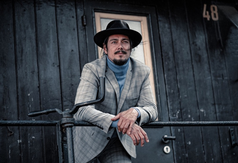 Chris wears hat Stetson, suit Selected Homme, and sweater Bruno Banani.