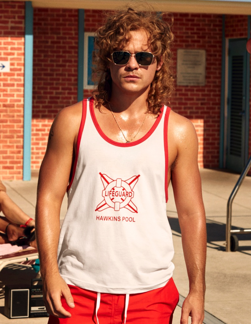 Dacre Montgomery wears a tank and red swim shorts from H&M's Stranger Things collaboration.