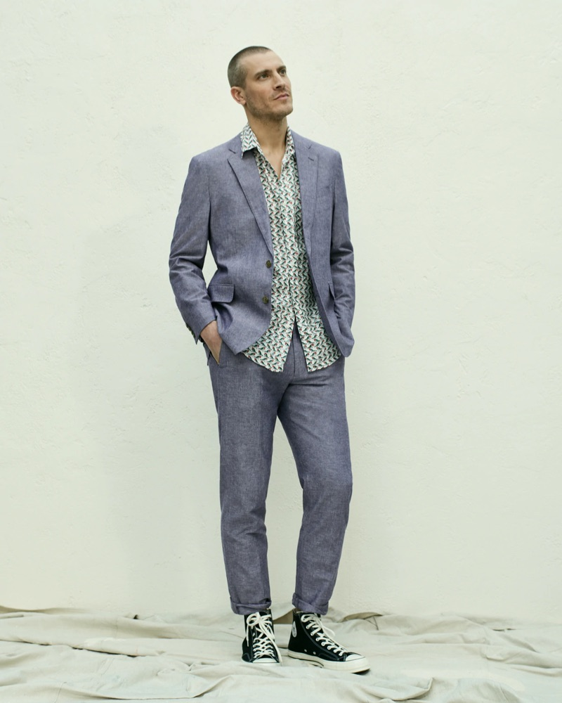 Mike Guenther wears a J.Crew Ludlow slim-fit unstructured suit jacket in cotton-linen with matching suit pants. He also dons a J.Crew short-sleeve linen shirt with a baby birds print and Converse Chuck Taylor All Star '70 high-top sneakers.