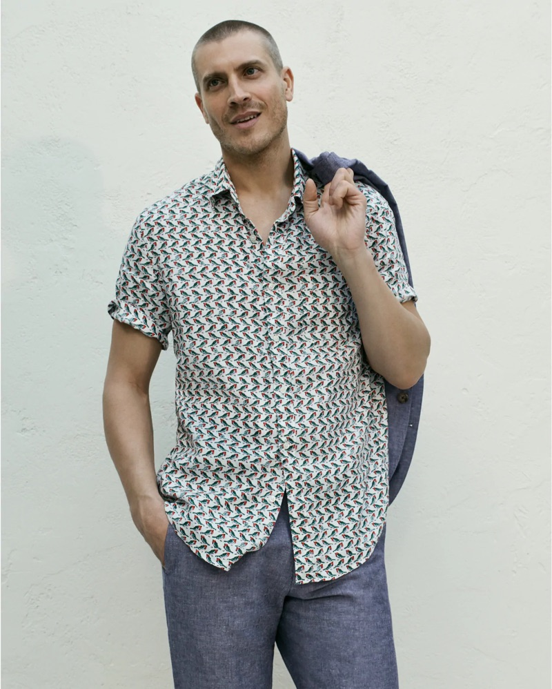 Front and center, Mike Guenther sports a J.Crew Ludlow slim-fit unstructured suit jacket in cotton-linen with matching suit pants. A J.Crew short-sleeve linen shirt with a baby birds print completes his look.