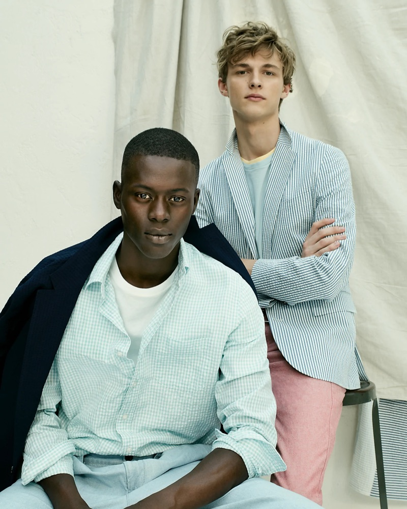 Left: Alpha Dia wears a blue J.Crew seersucker shirt, essential crewneck t-shirt, indigo chambray double-pleated pants, and a Ludlow slim-fit unstructured blazer in stretch seersucker. Right: Max Barczak sports a blue J.Crew Ludlow slim-fit unstructured blazer in seersucker with two essential crewneck t-shirts. The model also wears the brand's 770 straight-fit chino pants in stretch chambray.