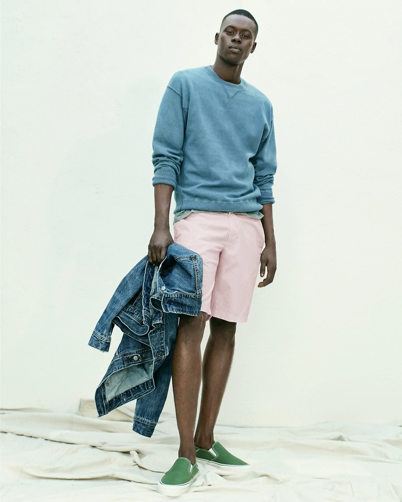 Casual for summer, Alpha Dia sports a J.Crew classic denim jacket with a blue side-panel crewneck sweatshirt. Alpha also wears pink shorts and green Vans slip-on sneakers.