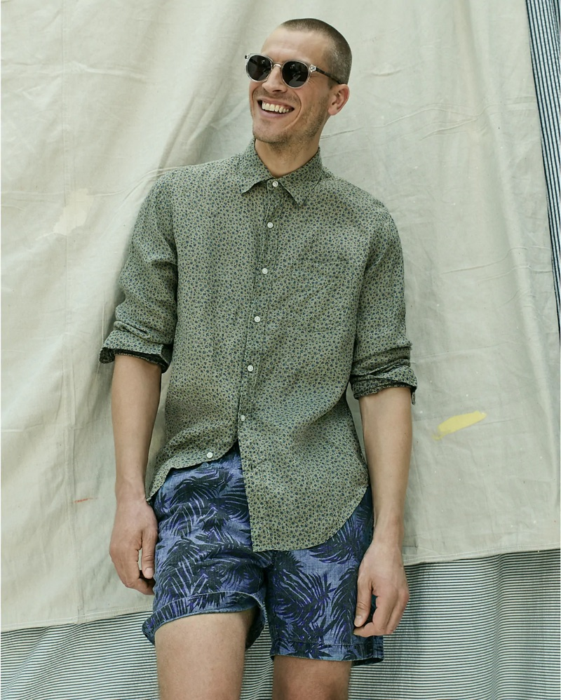 All smiles, Mike Guenther dons a J.Crew Albini Italian linen floral print shirt, indigo palm print dock shorts, and Wainscott sunglasses.