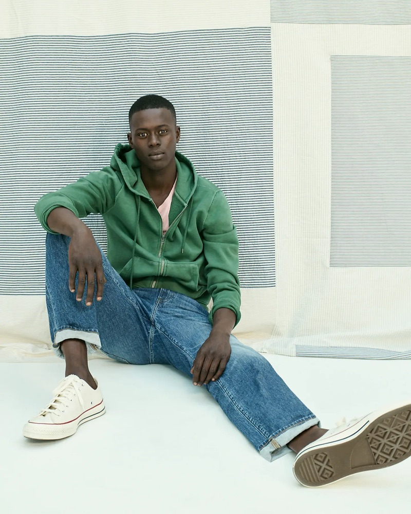 Going sporty, Alpha Dia wears a green J.Crew French terry full-zip hoodie, essential crewneck t-shirt, 1040 athletic-fit jeans, and Converse Chuck Taylor All Star '70 low-top sneakers.