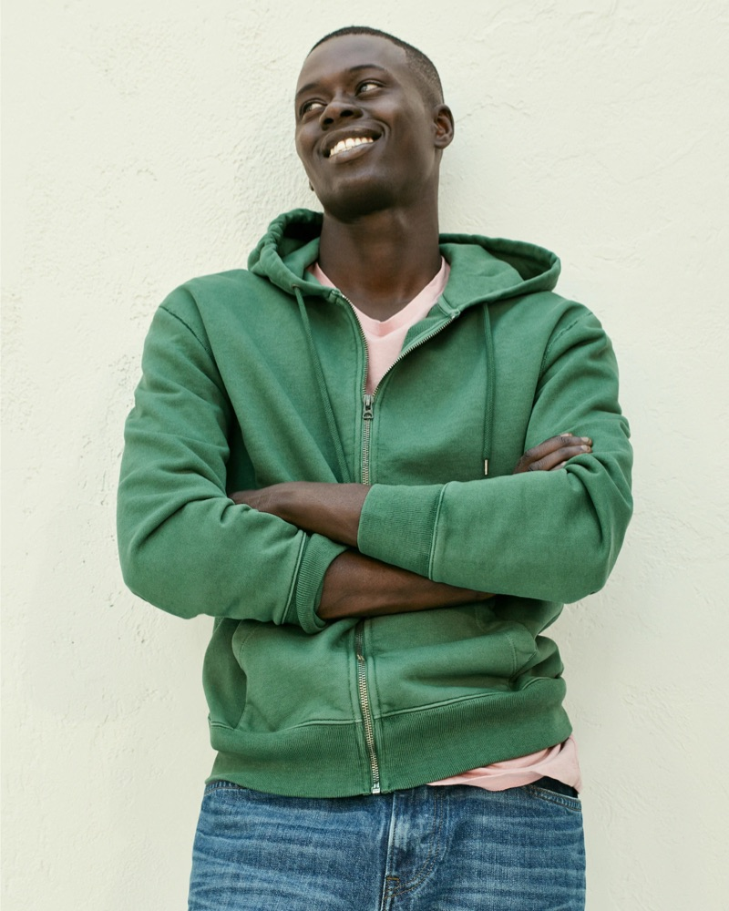 Crossing his arms, Alpha Dia rocks a green J.Crew French terry full-zip hoodie, essential crewneck t-shirt, and 1040 athletic-fit jeans.