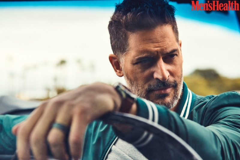 Getting behind the wheels of a car, Joe Manganiello wears an Eleventy jacket and Calvin Klein t-shirt with a Movado watch.