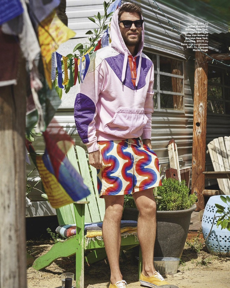 Mixing graphics, Liam Hemsworth rocks an Isabel Marant hoodie, Dries Van Noten swim shorts, Vans sneakers, and Jacques Marie Mage sunglasses.