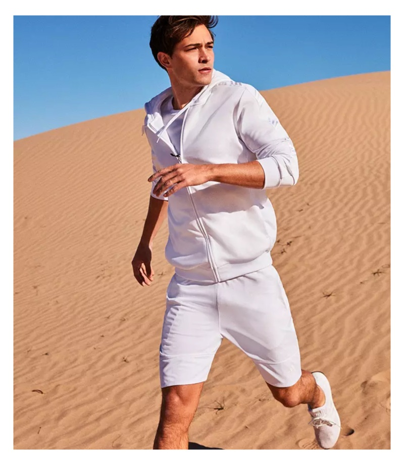 Embracing sporty style, Francisco Lachowski wears all white in a hoodie, tee, shorts, and knit sneakers.