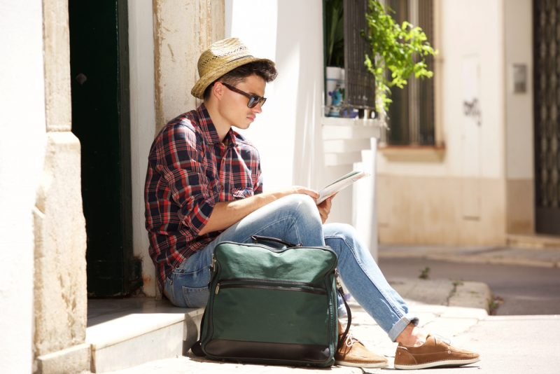 Man in Hat and Sunglasses Reading