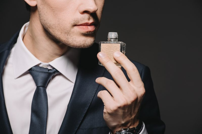 Man in Suit with Bottle of Fragrance
