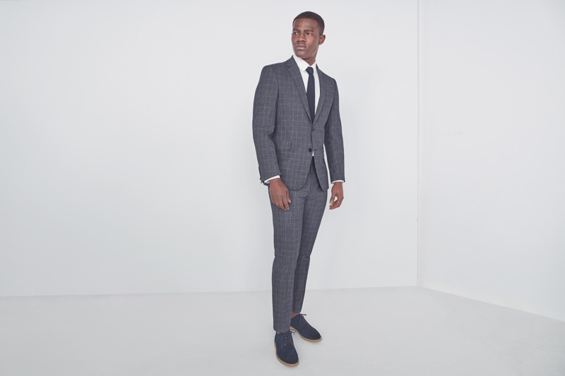 Donning a sharp suit, Kesse Donkor wears Marks & Spencer.