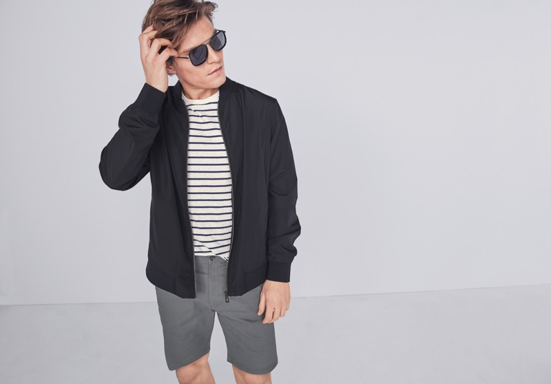 Sporting a bomber jacket, Oliver Cheshire wears a striped top and casual shorts from Marks & Spencer.