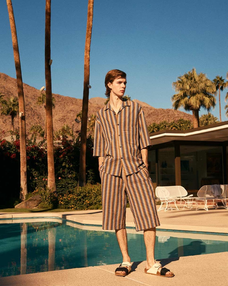 Sporting a coordinated look, Efraim Schröder wears a shirt and shorts by Lemaire with Rick Owens x Birkenstock sandals.