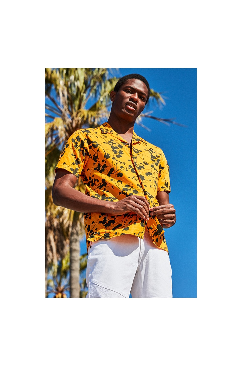 Standing out in yellow, Hamid Onifade dons an I.N.C. men's twig leaf camp collar shirt $55.