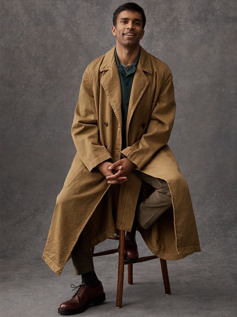 Sitting for a portrait, Nikesh Patel dons a Dries Van Noten trench coat, Mr P. camp-collar shirt, Etro t-shirt, and Thom Sweeney corduroy suit trousers. He also sports Mr P. derby shoes.