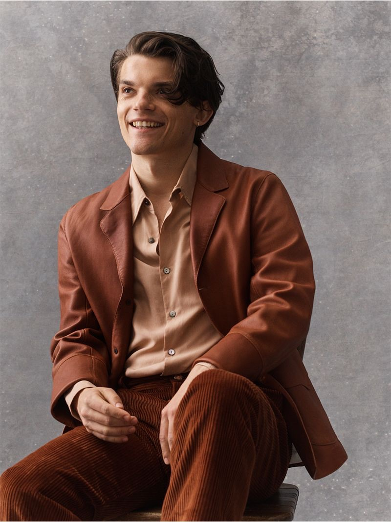 All smiles, Edward Bluemel wears a Loewe leather jacket, Save Khaki United shirt, and Séfr corduroy trousers.