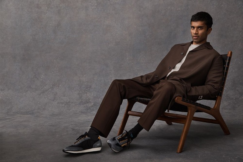 Embracing a rich brown hue, Nikesh Patel wears a Prada coat, trousers, and Milano 70 nylon and suede sneakers with a Beams Plus mélange mohair-blend sweater.